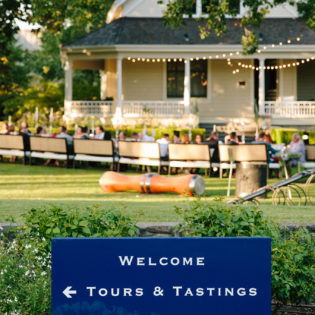 Blue welcome sign at St. Supéry estate with the Atkinson house in the background