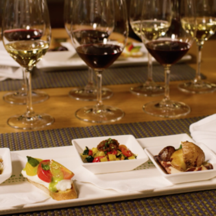 Rectangular plate with four vegetarian wine pairings With wine glasses filled in the background